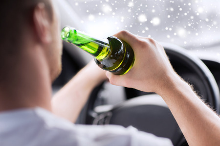 transportation, alcohol, vehicle and people concept - close up of man drinking alcohol while driving car Stock Photo