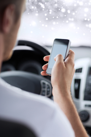 transportation, people, technology and vehicle concept - close up of man using smartphone while driving car photo