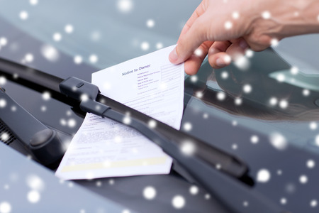 summons: transportation and vehicle concept - close up of male hand with parking ticket on car windscreen