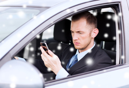close up of man using smartphone while driving car photo