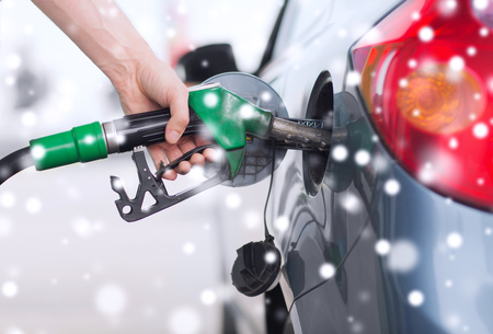 petrol station: transportation, tanking, people and vehicle concept - close up of male hand with fuel hose nozzle tanking car Stock Photo