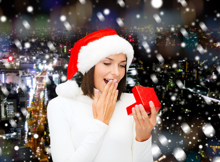 christmas, winter, happiness, holidays and people concept - smiling woman in santa helper hat with gift box over snowy night city background photo