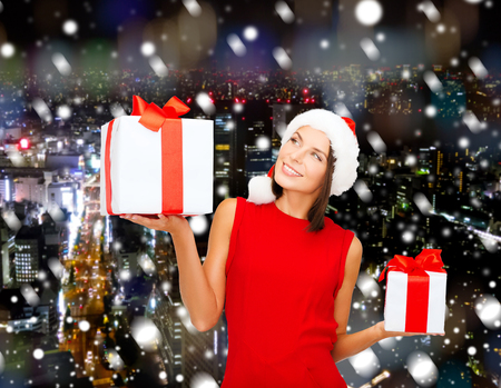 christmas, holidays, celebration and people concept - smiling woman in red dress with gift box over background photo