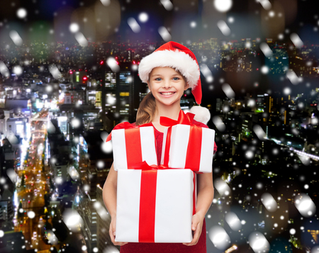 holidays, presents, christmas, childhood and people concept - smiling little girl in santa helper hat with gift boxes over snowy night city background photo