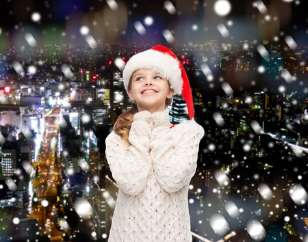 christmas, holidays, childhood and people concept - smiling girl in santa helper hat over snowy night city background photo