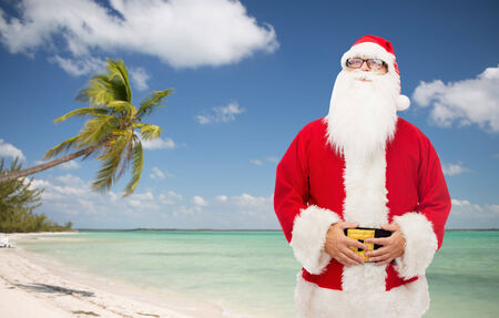 man in costume of santa claus over tropical beach background photo