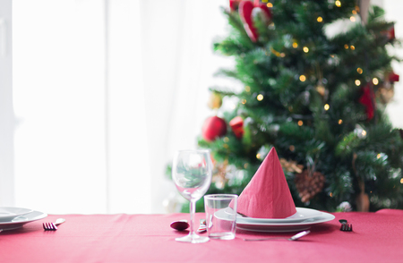 red tablecloth: holidays, celebration and home concept - close up of room with christmas tree and decorated table