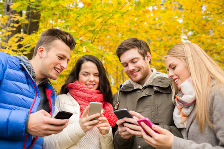 smiling teenagers: season, people, technology and friendship concept - group of smiling friends with smartphones in autumn park Stock Photo