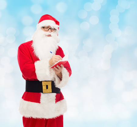 christmas, holidays and people concept - man in costume of santa claus with notepad and pen over blue lights background photo