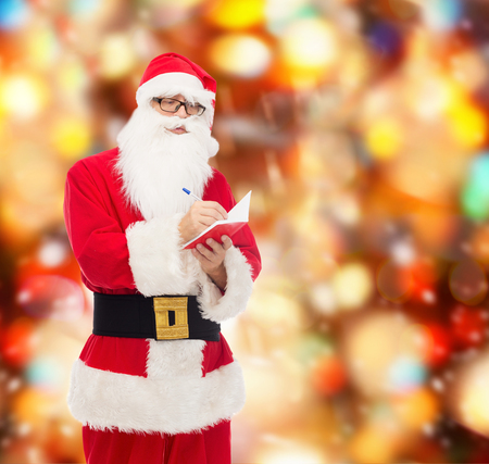 man in costume of santa claus with notepad and pen over red lights background photo