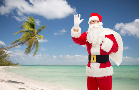 christmas, holidays, gesture, travel and people concept - man in costume of santa claus with bag waving hand over tropical beach background photo