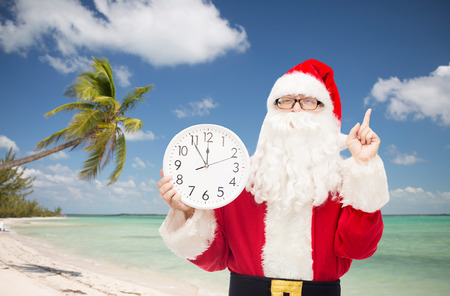nicolas: christmas, holidays, travel and people concept - man in costume of santa claus with clock showing twelve pointing finger up over tropical beach background