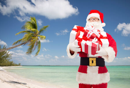 nicolas: man in costume of santa claus with gift boxes over tropical beach background