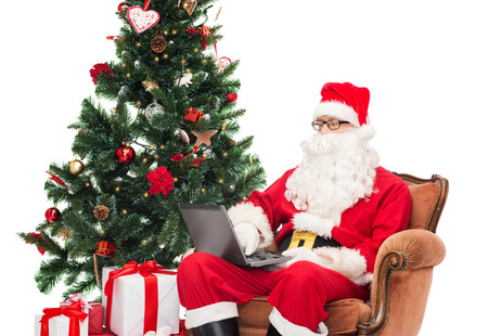 man in costume of santa claus with laptop computer, gifts and christmas tree sitting in armchair photo