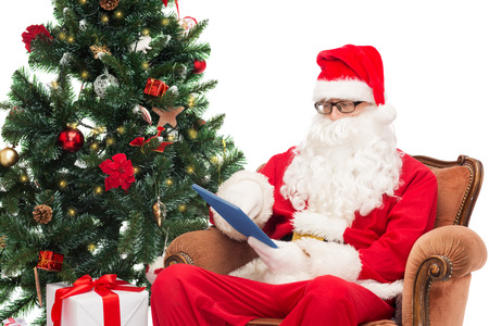 man in costume of santa claus with tablet pc computer, gifts and christmas tree sitting in armchair photo