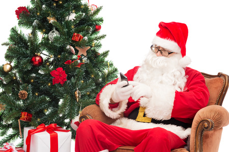 nicolas: man in costume of santa claus with smartphone, presents and christmas tree