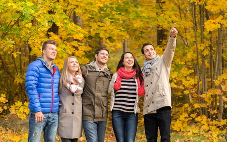 love, relationship, season, friendship and people concept - group of smiling men and women hugging in autumn park photo