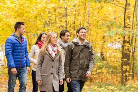 Amour, relation, la saison, l'amitié et les gens notion - groupe de sourire des hommes et des femmes marchant dans le parc de l'automne Banque d'images - 32785390