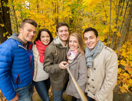 to stick: season, people, technology and friendship concept - group of smiling friends with smartphone or digital camera and selfie stick taking picture in autumn park
