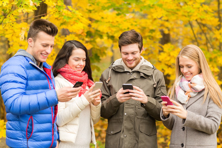 season, people, technology and friendship concept - group of smiling friends with smartphones in autumn park photo