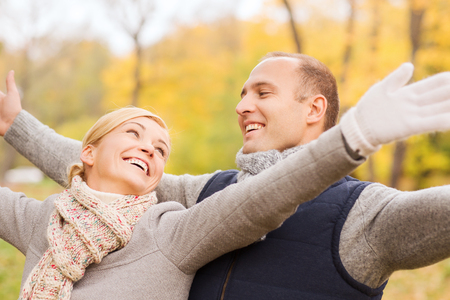love, relationship, family and people concept - smiling couple in autumn park photo