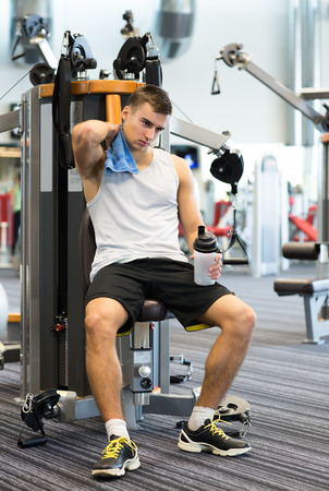 sport, fitness, equipment, lifestyle and people concept - man exercising on gym machine photo