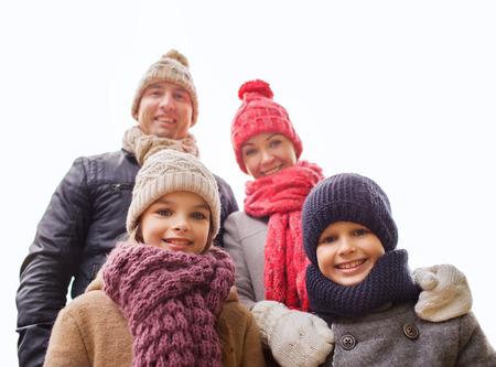 ropa de invierno: la familia, la infancia, la temporada y la gente concepto - familia feliz al aire libre