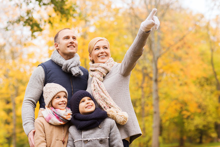 family, childhood, season, gesture and people concept - happy family pointing finger in autumn park photo