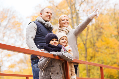 family, childhood, season and people concept - happy family pointing finger in autumn park photo