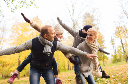 having: family, childhood, season and people concept - happy family having fun in autumn park