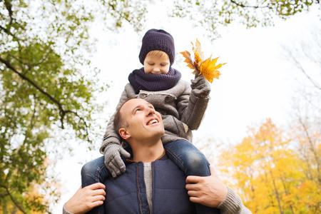 padres hablando con hijos: la familia, la infancia, la temporada y la gente concepto - feliz padre e hijo se divierten en parque del oto�o