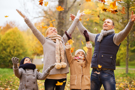 happiness: family, childhood, season and people concept - happy family playing with autumn leaves in park