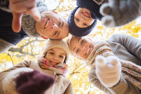 caes: la familia, la infancia, la estaci�n, el gesto y el concepto de la gente - familia feliz que se�ala el dedo en usted en el oto�o de parque