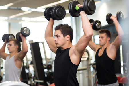 weightlifting equipment: sport, fitness, lifestyle and people concept - group of men with dumbbells in gym Stock Photo