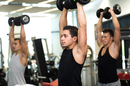 body work: sport, fitness, lifestyle and people concept - group of men with dumbbells in gym Stock Photo