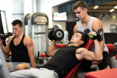 sport, fitness, lifestyle and people concept - group of men with dumbbells in gym Foto de archivo