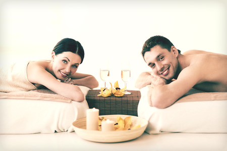 Glasses of champagne and candles: picture of couple in spa salon drinking champagne