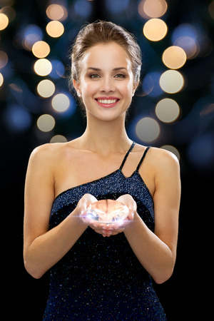 people, holidays, jewelry and glamour concept - smiling woman in evening dress holding big diamond over night lights background photo