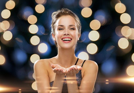 the smile: people, holidays, advertisement and luxury concept - laughing woman in evening dress holding something imaginary over night lights background