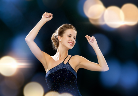 raised arms: people, party, holidays and glamour concept - smiling woman dancing with raised hands over night lights background Stock Photo
