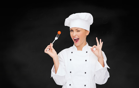 ok sign: cooking and food concept - smiling female chef, cook or baker with fork and tomato showing ok sign Stock Photo