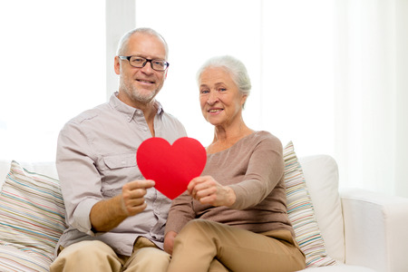 shape heart: family, holidays, age and people concept - happy senior couple with little red paper heart shape cutout at home