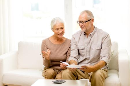 Familie, bedrijf, besparing, leeftijd en mensen concept - glimlachend senior paar met papieren en rekenmachine thuis