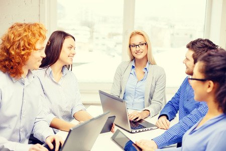 business, office and startup concept - smiling creative team with table pc and laptop computers working in office photo