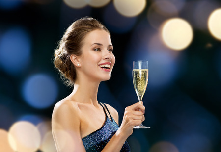 party, drinks, holidays, luxury and celebration concept - smiling woman in evening dress with glass of sparkling wine over night lights background photo