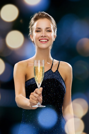 party, drinks, holidays, luxury and celebration concept - smiling woman in evening dress with glass of sparkling wine over night lights background Imagens