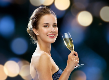 night life: party, drinks, holidays, luxury and celebration concept - smiling woman in evening dress with glass of sparkling wine over night lights background Stock Photo