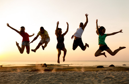 friendship, summer vacation, holidays, party and people concept - group of smiling friends dancing and jumping on beach Archivio Fotografico