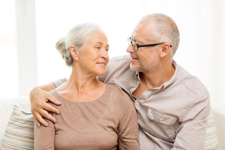 vejez feliz: la familia, las relaciones, la edad y el concepto de la gente - la feliz pareja senior abrazos en el sof� en casa