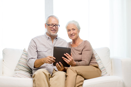 family, technology, age and people concept - happy senior\ couple with tablet pc computer at home